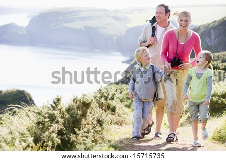 Family walking on cliffside path holding hands and smiling - stock photo