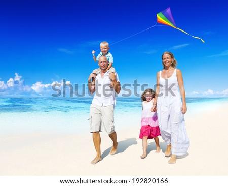 Family walking on the beach. - stock photo