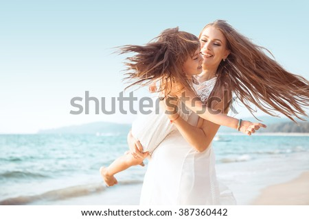 Family walking on the evening beach during sunset. Child with mom. - stock photo