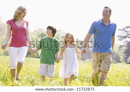 Family walking outdoors holding hands - stock photo