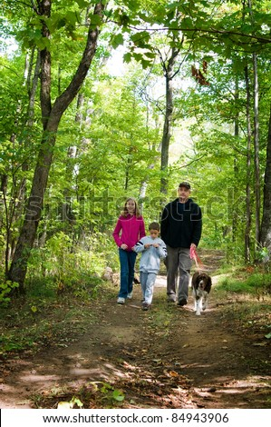 family walking their dog on a forest path