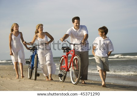 Family walks down the beach as mother and father push their bicycles. Horizontal shot.