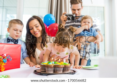 Family watching girl blowing out candles on birthday cake at home