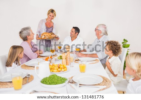 Family watching the roast turkey for dinner