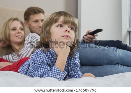 Family watching TV in bedroom - stock photo