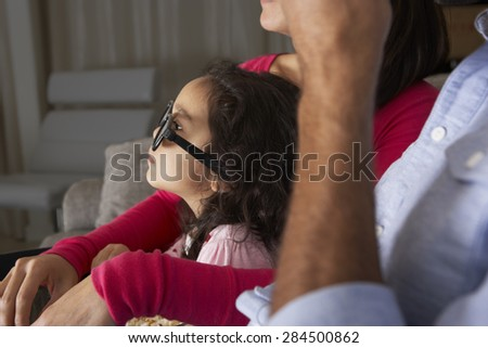 Family Watching TV Wearing 3D Glasses And Eating Popcorn - stock photo