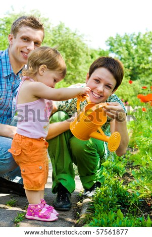 Family watering flowers in the garden - stock photo