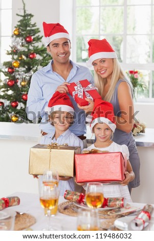 Family wearing santa hats holding christmas presents - stock photo