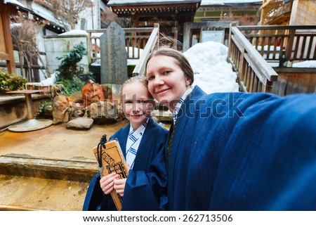 Family wearing yukata Japanese kimono making selfie at street of onsen resort town in Japan. Translation of text on wooden plate: passport for round bath visit to protect you from bad luck. - stock photo
