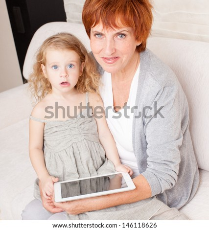 Family wiht tablet computer at sofa. Grandmother and little girl at home on sofa - stock photo