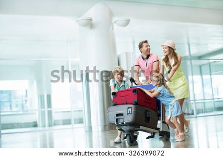 Family with a suitcase at the airport - stock photo