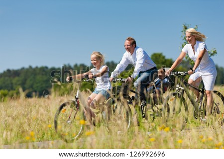 Family with baby and and daughter having a weekend excursion on their bikes on a summer day in beautiful landscape - stock photo