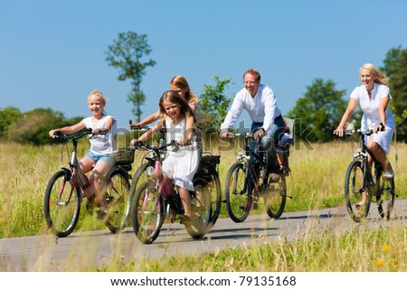 Family with baby and three girls having a weekend excursion on their bikes on a summer day in beautiful landscape - stock photo