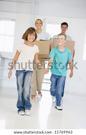 Family with boxes moving into new home smiling - stock photo