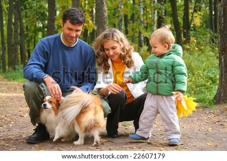 family with boy and dog in autumn wood