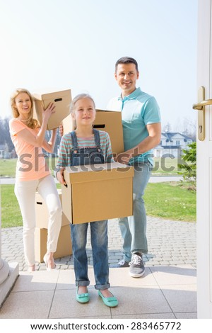 Family with cardboard boxes entering new house - stock photo