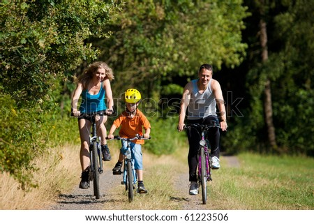 Family with child on their bikes on a summer day in sport outfit, FOCUS ON SON ONLY - stock photo