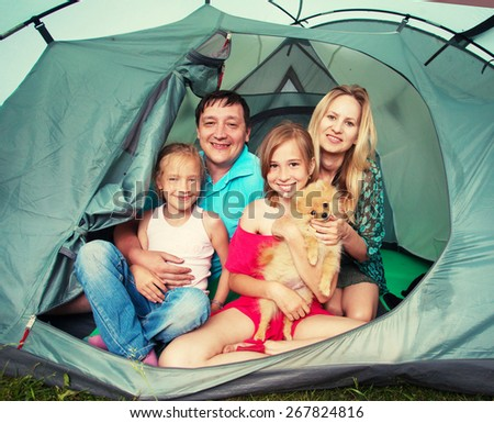 Family with children in a tent. Camping. Happy parents with kids at summer vacations - stock photo