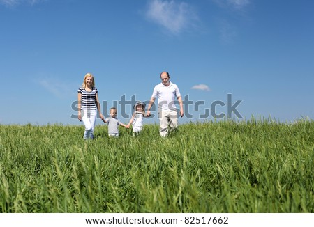 family with children in summer day on the meadow