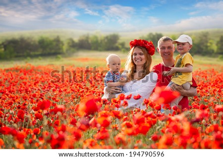 Family with children in the field of red poppies - stock photo