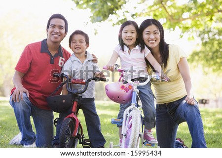 Family with children on bikes outdoors smiling - stock photo
