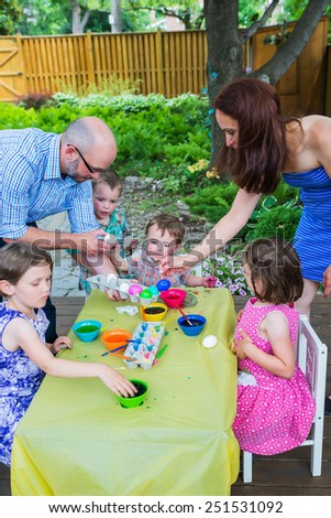 Family with children painting and decorating eggs together during the spring season in a outdoor garden setting.  Mother and father help the kids color dye their Easter eggs.  Part of a series.  - stock photo