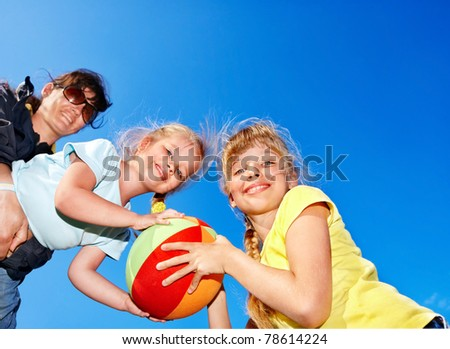 Family with children playing with ball in park. - stock photo