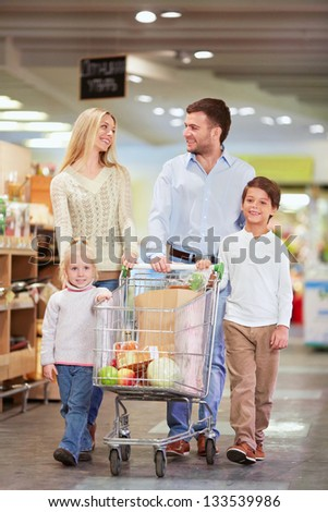 Family with children products with a cart in the store