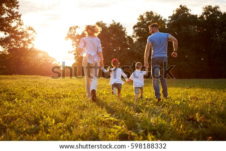 Family with children running together in nature, back view