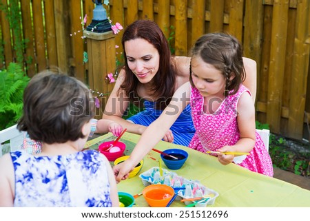 Family with children together painting and decorating eggs outside during the spring season in a garden setting.  Happy mother looks on as her kids color dye their Easter eggs.  Part of a series.   - stock photo