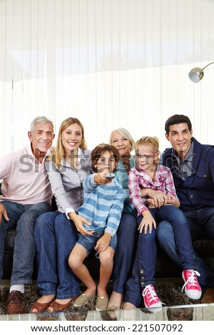 Family with children watching Smart TV with remote control in living room - stock photo