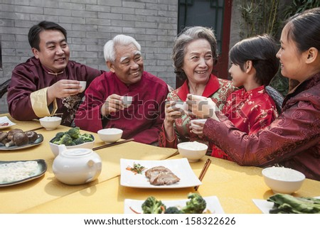 Family with cups raised toasting over Chinese meal - stock photo
