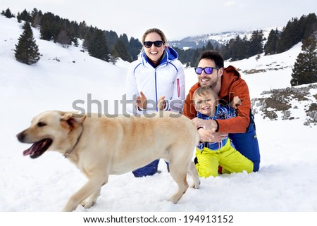 family with dog having fun in the snow - stock photo