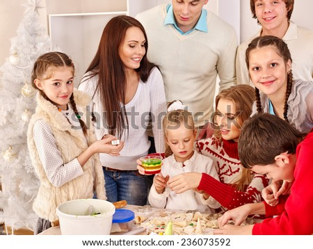 Family with father and children rolling dough in the kitchen. - stock photo