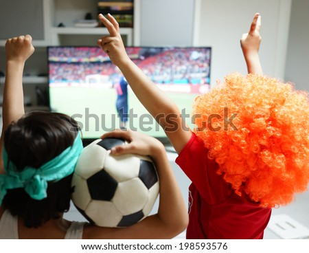 Family with football watching soccer world cup game 2014 on tv in living room - stock photo