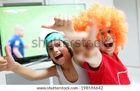 Family with football watching soccer world cup game on tv in living room - stock photo