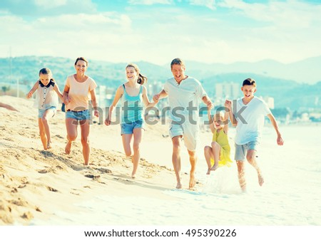 Family with four kids happily running together on beach on summer day