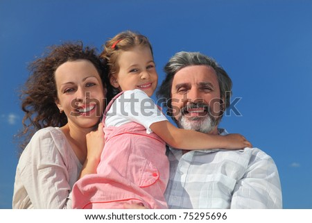 family with girl, mother and grandfather smiling and embracing, blue sky