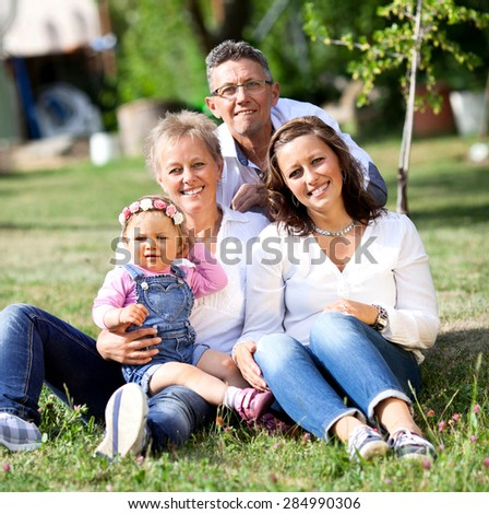 Family with Grandparents and little girl in outside in garden