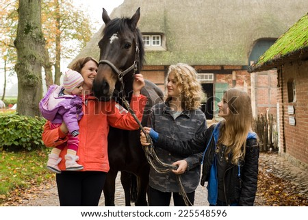 Family with horse on the farm - stock photo