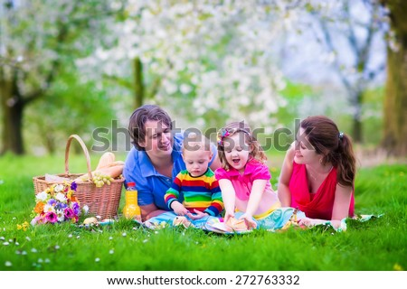 Family with kids having picnic outdoors. Parents with two children relax in a summer garden. Mother, father, little girl and baby boy eat sandwich and fruit, drink juice for healthy lunch in a park. - stock photo