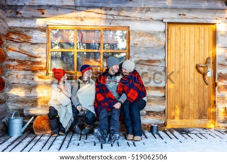 Family with kids outdoors on beautiful winter day in front of log cabin vacation house