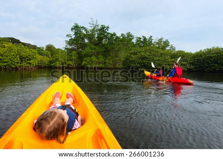 Family with kids paddling on colorful kayaks at mangroves during summer vacation - stock photo
