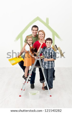 Family with kids painting their new home - smiling and holding utensils - stock photo