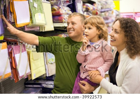 family with little girl buy bedding in supermarket - stock photo