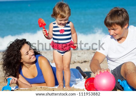 Family with little girl playing on the beach - stock photo