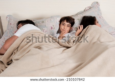 Family with mobile phone in the bed - stock photo