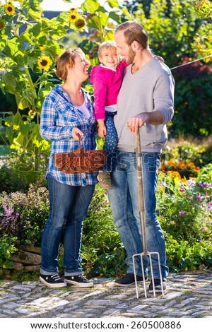 Family with mother, father and daughter gardening in garden  - stock photo