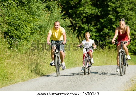 Family with one child riding their bicycles on a summer day - stock photo