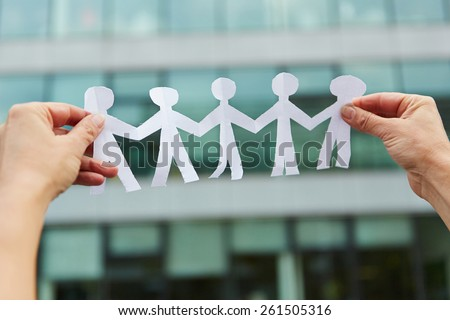 Family with people made of paper held in hands - stock photo